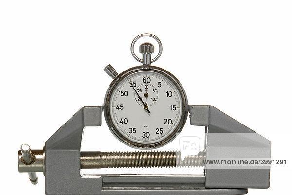 Stoppuhr in Schraubstock eingeklemmt  Symbolbild für Zeitdruck