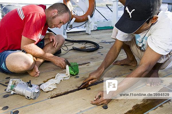 Matrosen versiegeln die Planken auf einem Schiff  Indonesien