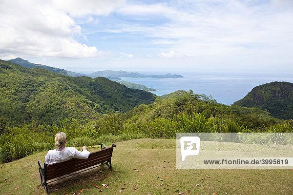 Frau sitzt auf einer Bank im Nationalpark Morone  hinten der Strand von Grand Anse Insel Mahe  Seychellen  Indischer Ozean  Afrika