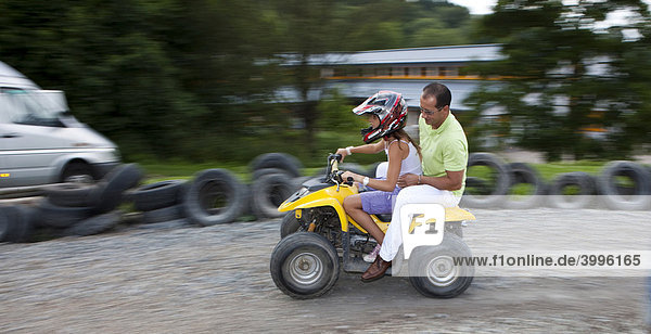 Father and daughter riding a quad bike  Hesse  Germany  Europe