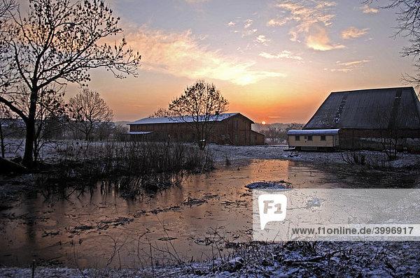 Sunrise over an old farmstead  at front a frozen pond  Othenstorf  Mecklenburg-Western Pomerania  Germany  Europe