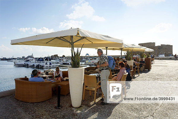 People in a cafe with sun umbrellas at the shore promenade  citadel  Paphos  Pafos  Cyprus  Europe