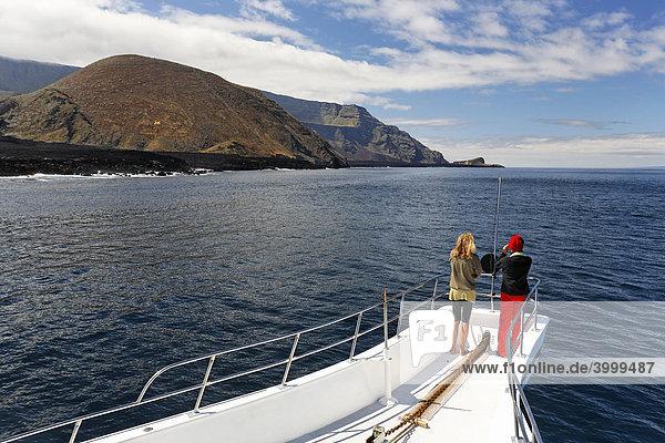 Zwei Frauen stehen am Bug vom Schiff Reina Silvia  Vulkankegel  Nordspitze  Ponta de Sao Vicente  Insel Isabella  Galapagos Archipel  Ecuador  Südamerika