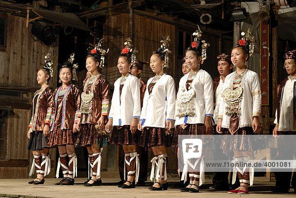 Männer und Frauen in Tracht eines offiziellen Dong-Minderheitenensembles in Zhaoxing in Guizhou  China  Asien