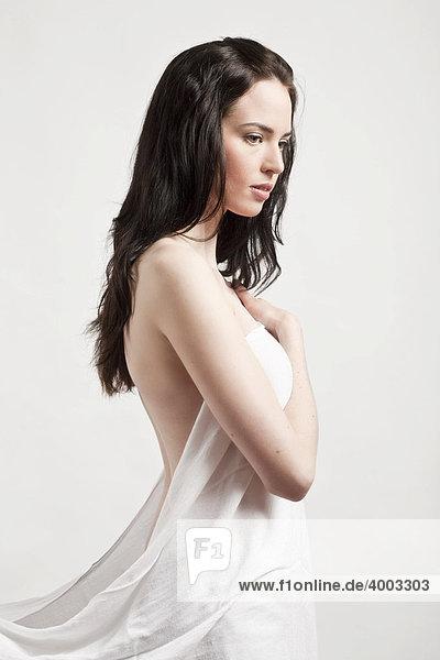 Junge dunkelhaarige Frau mit Decke um den Körper gewickelt