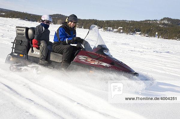 Eine Frau in den Vierzigern und ein sechsjähriges Mädchen auf einer Schneemobil-Tour in Kiruna  Lappland  Nord-Schweden  Schweden