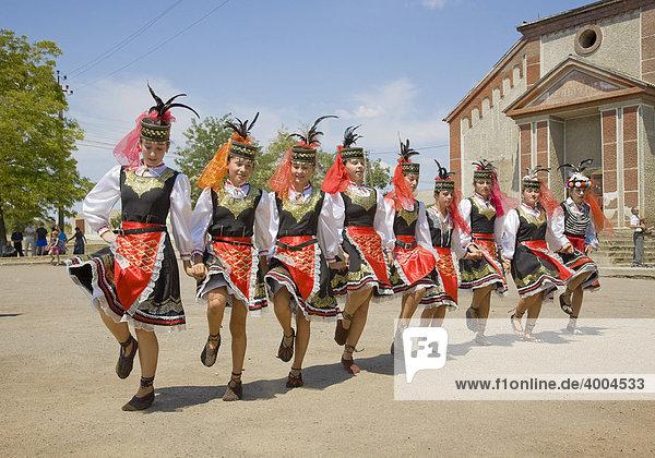 Young girls in traditional Ukrainian costume dancing in front of the parish hall in Pltozk  Ukraine