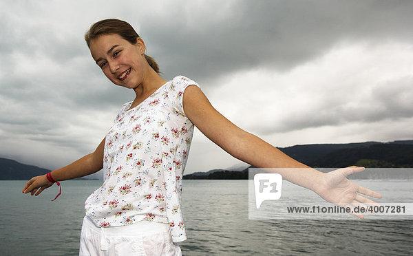Junges Mädchen breitet Arme aus vor See