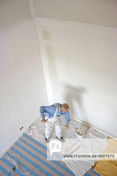 Maler beim Anbringen von Wandfarbe