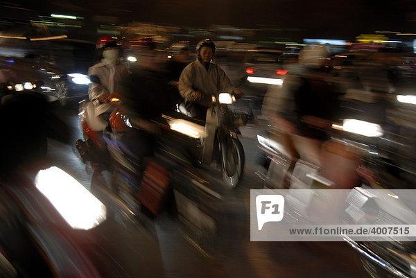 Moped riders in dense traffic at night  motion blur  Hanoi  Vietnam  Asia