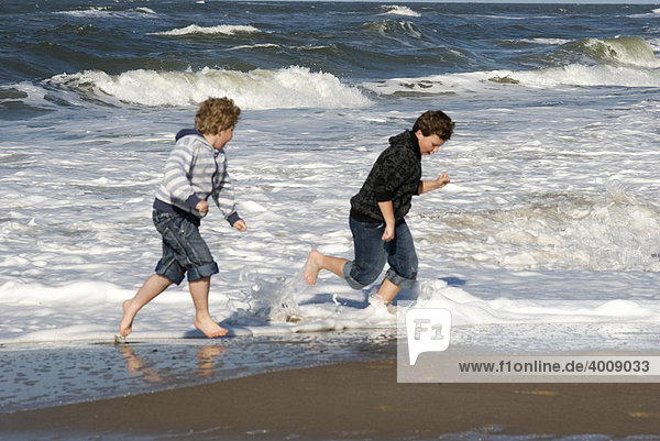2 boys surprised by a wave on the North Sea coast of Holme Land  Jutland  Denmark  Europe