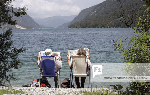 Pensioner couple reading the newspaper on the bank of the Achensee Lake near Pertisau  Tyrol  Austria  Europe