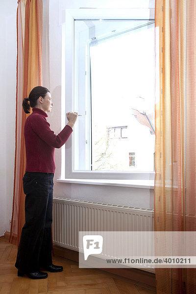 Eine junge Frau lüftet ihre Wohnung