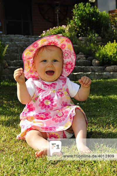 Toddler sitting on the lawn in a garden and playing