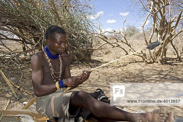 Ein Angehöriger der Hadzabe fertigt einen Jagdpfeil  Lake Eyasi  Tansania  Afrika