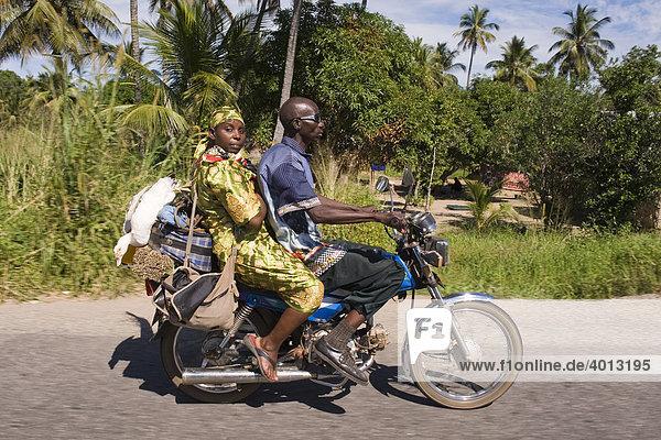Ein Mann und eine Frau transportieren ihre Einkäufe auf einem Motorrad  Quelimane  Mosambik  Afrika