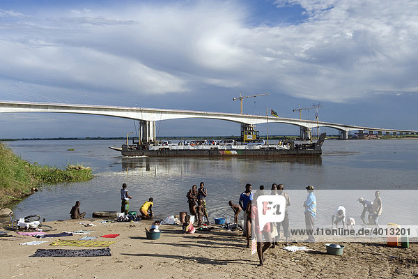 People washing clothes and bathing at the Zambezi riverbank  the new Zambezi bridge at back  Caia  Mozambique  Africa