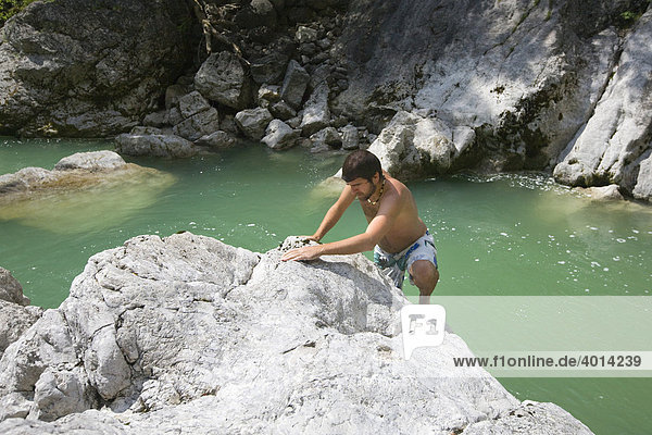Swimmer climbing a rock in the Brandenberger Ache River  North Tyrol  Austria  Europe