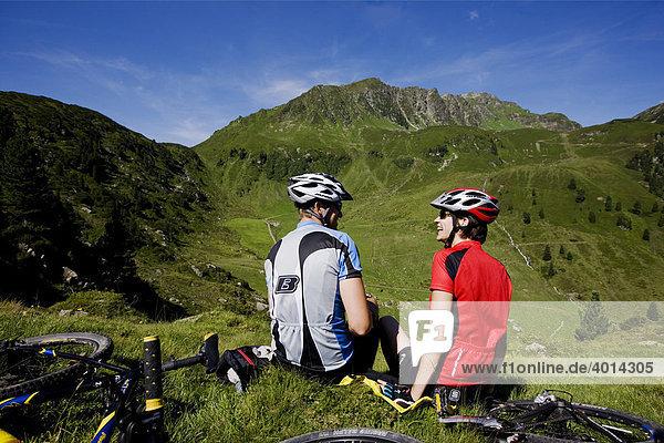 Mountainbiker machen Pause  dahinter der Galtenberg  Kitzbühler Alpen  Alpbachtal  Nordtirol  Österreich  Europa
