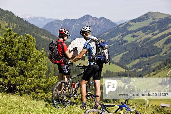 Mountainbiker suchen auf Landkarte den Weg  dahinter die Gratlspitze  Alpbachtal  Kitzbühler Alpen  Nordtirol  Österreich  Europa