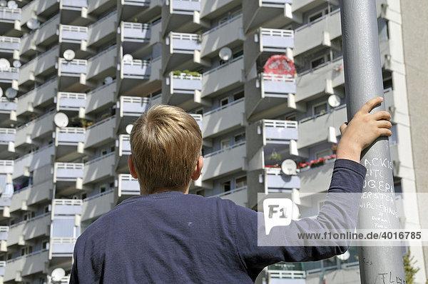 Ein Junge vor einem Wohnhochhaus mit Balkonen und Satellitenschüsseln  Trabantenstadt Chorweiler in Köln  Nordrhein-Westfalen  Deutschland  Europa