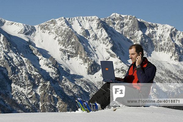 Mann am Gipfel mit Laptop