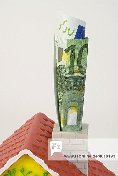 Miniaturhaus mit zusammengerolltem Geldschein im Schornstein  Symbolbild Energiesparen