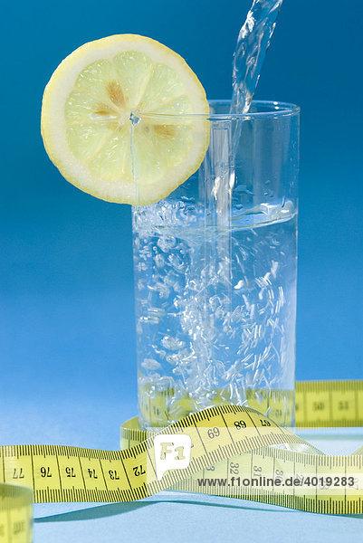 Wasserglas mit Zitrone und Maßband