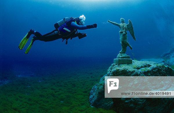 Taucher in einem Bergsee mit einer Engelsstatue