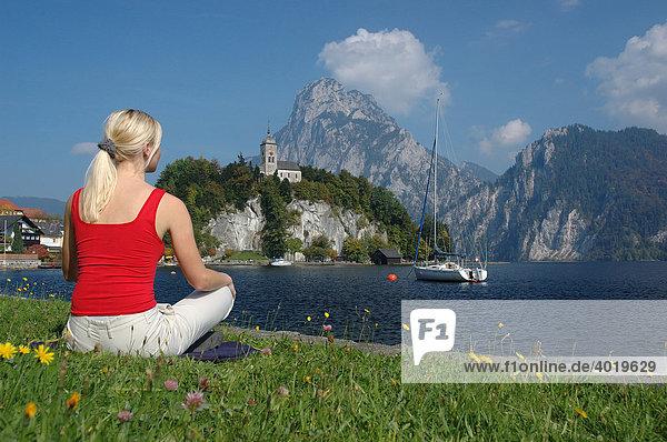 Junge blonde Frau entspannt sich am Traunsee  Salzkammergut  Oberösterreich  Österreich  Europa