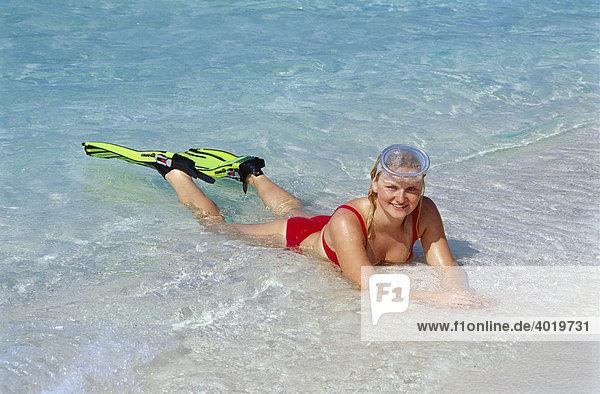 Blonde Frau  20 Jahre  mit Flossen und Taucherbrille liegt im flachen Wasser  Summer Island Village  Nord-Male-Atoll  Malediven  Indischer Ozean