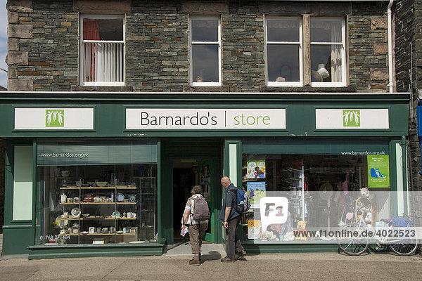Charity Shop  Bernardo's  zwei Senioren im Eingang  Keswick  Lake District  Cumbria  Nord England  Großbritannien  Europa