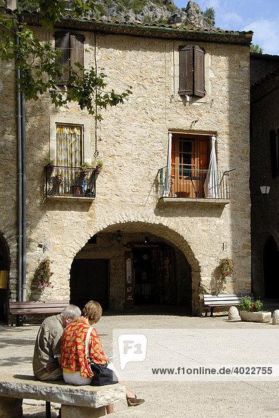 Zwei Personen auf Bank  altes Haus  Saint Guilhem le Desert  Herault  Languedoc-Roussillon  Frankreich  Europa