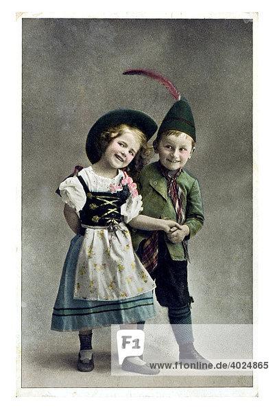 Valentin Grusskarte bayerisches Kinderpaar  bayerischer Junge und Märchen im Bayerndress mit Federhütchen Kniebundhosen und Dirndl