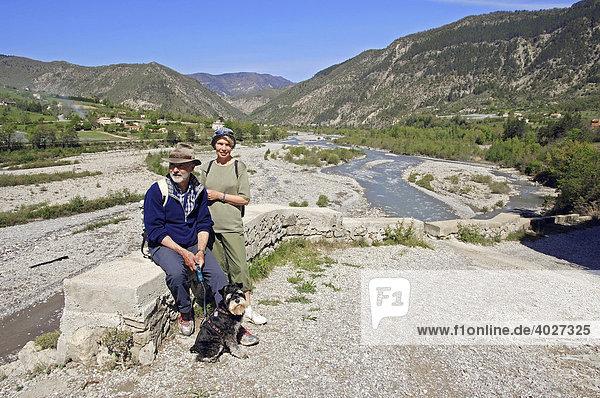 Paar mit Zwergschnauzer am Fluss Var  Entrevaux  Alpes-de-Haute-Provence  Provence-Alpes-Cote d'Azur  Südfrankreich  Frankreich  Europa