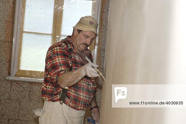 Plasterer at work  wave-like plaster  house construction  brickwork  interior works  plastering works