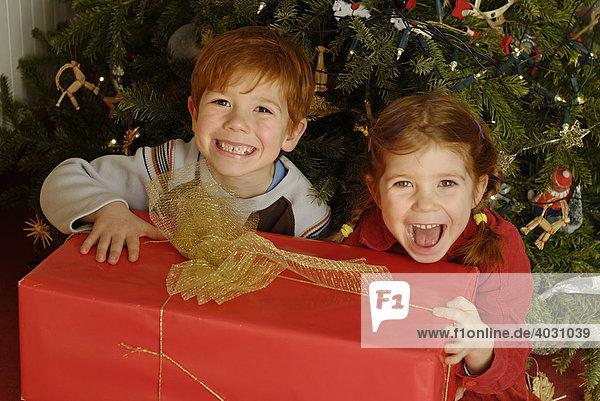 Geschwister mit einem großen Geschenk vor dem Weihnachtsbaum an Heiligabend