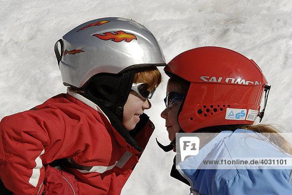 Zwei Kinder mit Helmen  Skifahren