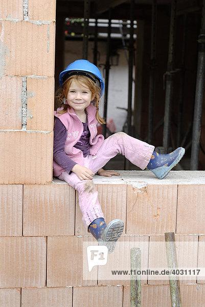 Kleines Mädchen mit Bauhelm sitzt in einem Rohbau auf einer Baustelle