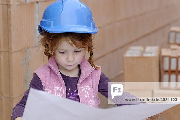 Mädchen mit Bauhelm studiert Bauplan in einem Rohbau auf einer Baustelle