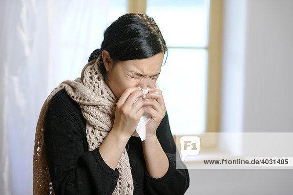 Junge Frau beim Naseputzen