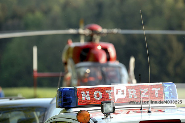 Illuminated sign  Emergency Doctor  on a rescue vehicle in front of a helicopter of the DRF or German Air Rescue  Frickenhausen  Baden-Wuerttemberg  Germany