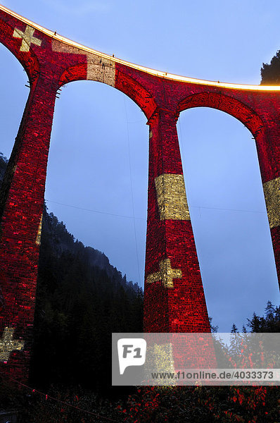 Irrigation water viaduct lit up with the national flag motif to celebrate the acceptance of the Rhaetische Bahn Railway in Albula/Bernina as a UNESCO World Heritage Site  Filisur  Graubuenden  Switzerland  Europe