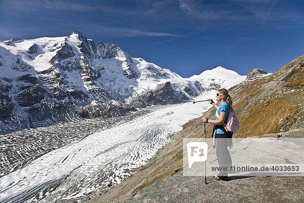 Frau zeigt auf die Pasterze  Gletscherzunge  links davon der Großglockner  3798m  und der Johannisberg  Nationalpark Hohe Tauern  Kärnten  Österreich  Europa