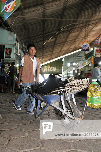 Child labour  boy transporting customers' purchases using a wheel barrow at the local market  Santa Cruz  Bolivia  South America