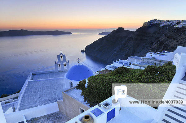 Stairway leading down to a white Greek church with a blue dome and a bell tower at sunset  Firostefani  Santorini  Cyclades  Greece  Europe