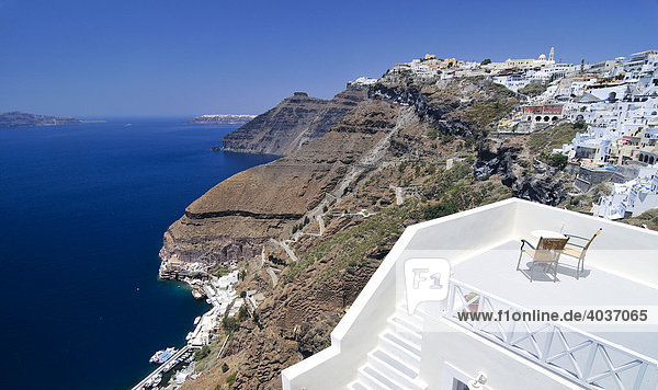 Terrace of a small hotel in front of the town of Thira  Fira  on the crater's edge wth a serpentine path to the port on the inner side of the caldera with a steep drop to the blue sea  Santorini  Cyclades  Greece  Europe