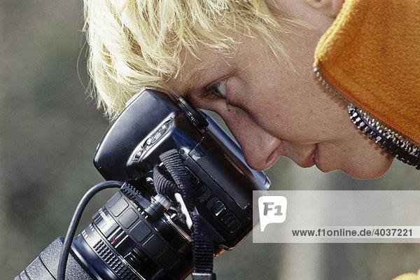 Blonde Frau blickt durch Spiegelreflexkamera
