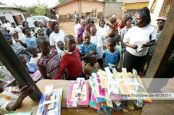 Women distributing school materials to school children  Women's Education Centre  Bamenda  Cameroon  Africa