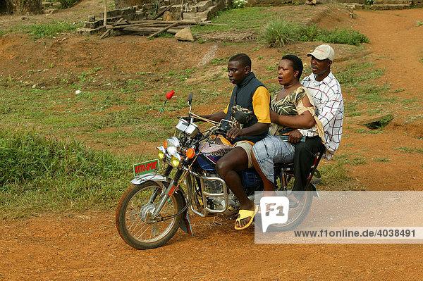 Zwei Männer und eine Frau auf dem Motorad  Hauptstraße in Manyemen  Kamerun  Afrika